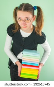 Teen girl with a stack of books against light green background