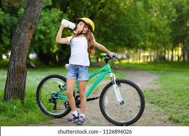 Teen girl standing in a helmet near the bike with a bottle of water in the summer