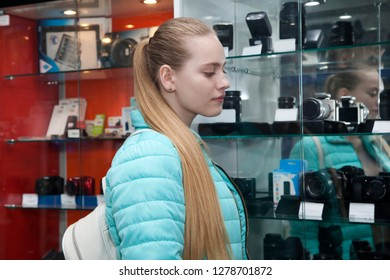 Teen girl standing near showcase with photo cameras. Young woman in shop phototechnique chooses a digital equipment
