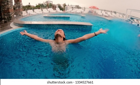 Teen girl standing under the rain in luxury swimming pool during summer vacation