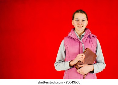 Teen girl staying with a book against red background
