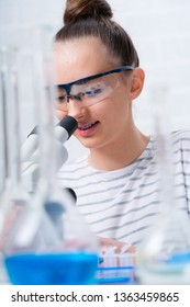 Teen girl student caring out experiments in chemistry class.high