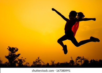 Teen girl in superhero costume jumping in the evening on the nature