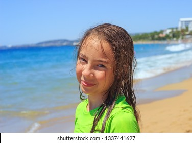 Teen girl surfing on tropical beach. Child on surf board on ocean wave. Active water sports for Teenager.