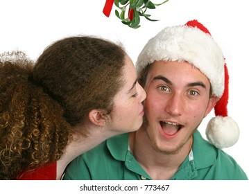 A teen girl surprising a teen boy with a kiss under the mistletoe.  Isolated.