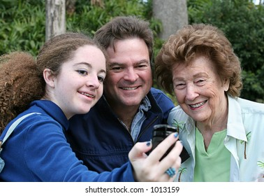 A teen girl takes a picture of herself, her father, and her grandmother with her new camera phone.