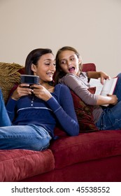 Teen girl texting on mobile phone while younger sister reads book