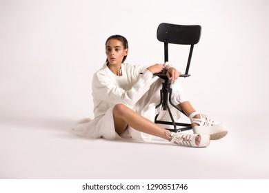 Teen girl in trendy clothes sitting on the floor. Translation of words: cosmos, оn fire