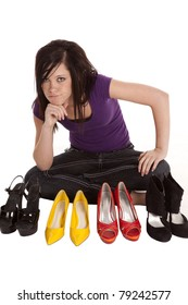 A teen girl is trying to figure out which shoes to wear.