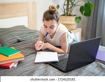 Teen girl uses laptop at home. Distance learning concept.