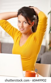 Teen girl using laptop computer browsing internet at home looking at camera smiling.