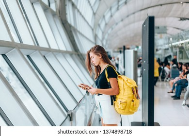 Teen girl using smarthphone while waiting for international flight in airport departure terminal. Young passenger with backpack travelling on airplane. Teenager tourizm abroad alone concept.