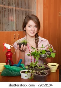 Teen girl with various seedlings at home