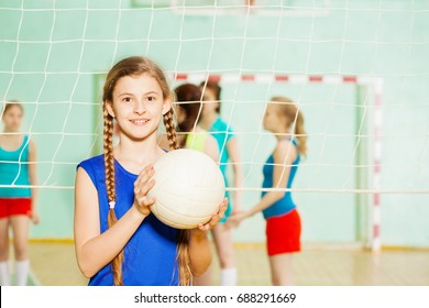 Teen girl with volleyball ball in sports hall