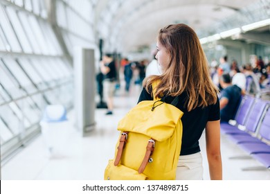 Teen girl waiting for international flight in airport departure terminal. Young passenger with backpack travelling on airplane. Teenager tourizm abroad alone concept.