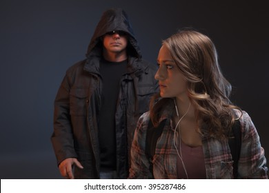 Teen girl is walking alone and senses something is wrong.  She looks over her should and sees a stranger behind her, about to attack.