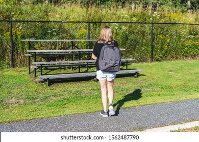 Teen girl walking to a set of bleachers near her school while wearing a backpack and holding binders.