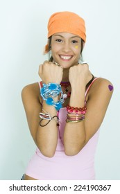 Teen girl wearing lots of accessories, holding up forearms, smiling at camera, portrait