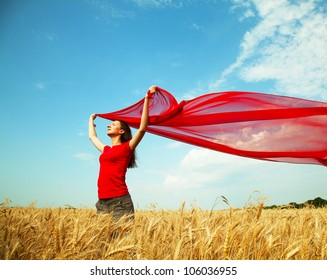 Teen girl at a wheat field with red fabric