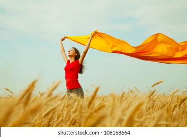 Teen girl at a wheat field with yellow fabric