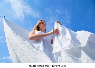 Teen girl in white dress is hung up sheets on clothesline. On blue sky background. View from below