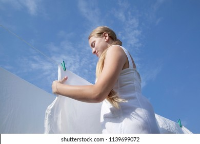 Teen girl with white sheets on background of blue sky. Drying clean laundry in rope outdoors. View from below