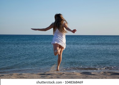 Teen girl in a white sundress running on sand. Evening on the beach. Back view