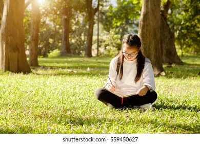 Teen Girl write on a book in park