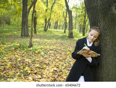 Teen girl writes a poetry in gold autumn park