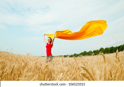 Teen girl with yellow fabric at the wheat field in sunny day