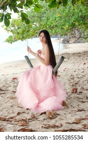 Teen girl or young biracial woman on Hawaiian beach wearing long flowing pink dress or gown sitting on swing