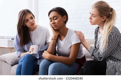 Teen girls comforting their upset friend, discussing problems and gossiping at home