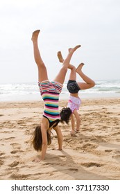 teen girls doing hand stand on beach