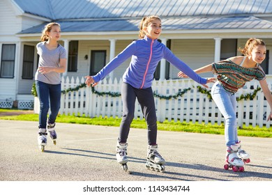 Teen girls group rolling skate in the street outdoor