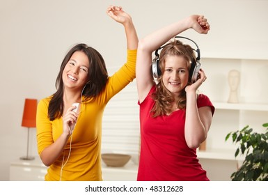 Teen girls listening to music having fun together at home dancing smiling, eye contact.