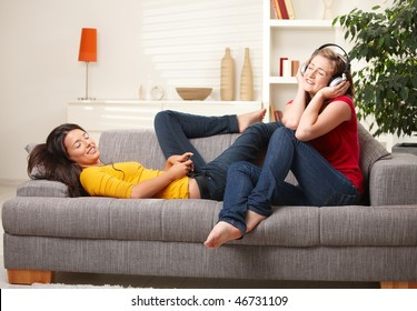Teen girls listening music on earphones and headphones sitting together on couch  at home with closed eyes smiling.