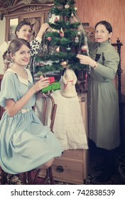 Teen girls with mother decorating Christmas tree at home