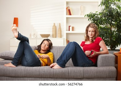 Teen girls relaxing on sofa at home listening to music.