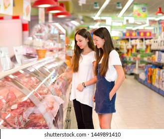 Teen girls shopping in the supermarket. Choosing daily product