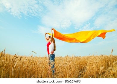 Teen girls at a wheat field with yellow fabric