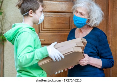 Teen grandson in mask gives grandmother food boxes of pizzas through the doorway of a house. Volunteer helps single elderly people. Family support, caring. Quarantined, isolated. Coronavirus covid-19