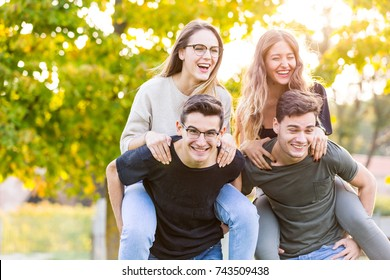 Teen group of friends together at park after school, having fun with a piggyback ride. Lifestyle and friendship concepts