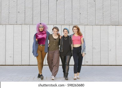 teen group of women wearing colorful clothes hugging and walking on the street