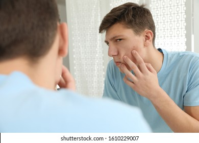 Teen guy with acne problem near mirror indoors