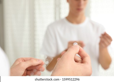 Teen guy using acne healing patch near mirror indoors, focus on hands