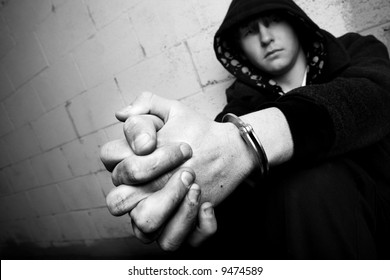 teen in handcuffs, young teen against wall with dirty hands and handcuffs, converted to black and white with slight added grain. focus on cuffs.