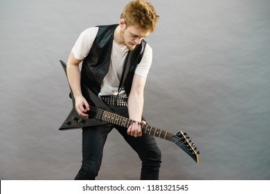 Teen hardcore man wearing metal outfit playing on electric guitar heavy rock music.