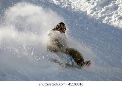 Teen having a wilde toboggan ride in the powder snow