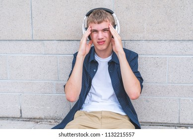 Teen with a headache listening to music while sitting on the ground against a wall.