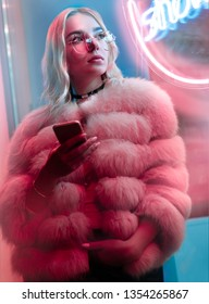 Teen hipster girl in fur glasses use cellphone mobile event dating app looking away stand near neon street sign, teenager young woman holding phone text messages in city night light glow, back to 80s